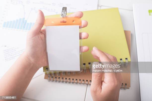 Cropped Image Of Woman Holding Plastic Badge Over Spiral Notebooks At Table