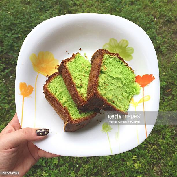 Cropped Image Of Woman Holding Plate With Slices Of Pandan Cake