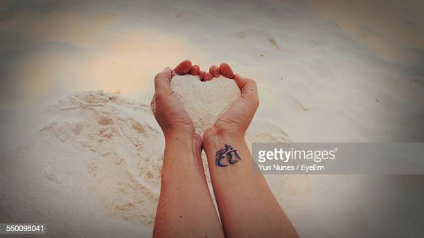 Cropped Image Of Woman Holding Sand With Heart Shape At Beach
