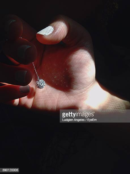 Cropped Image Of Woman Holding Silver Pendant In Sunlight