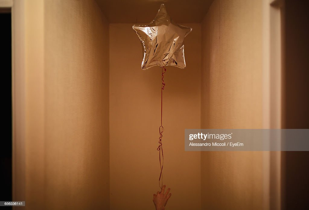 Cropped Image Of Woman Holding Star Shape Helium Balloon : Stock Photo