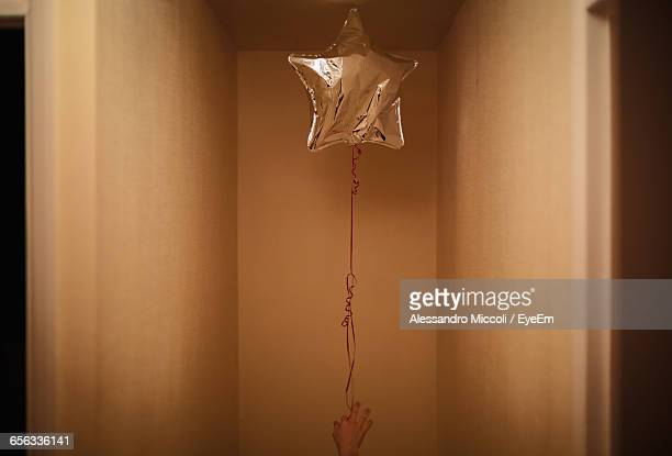 cropped image of woman holding star shape helium balloon - alessandro miccoli stockfoto's en -beelden