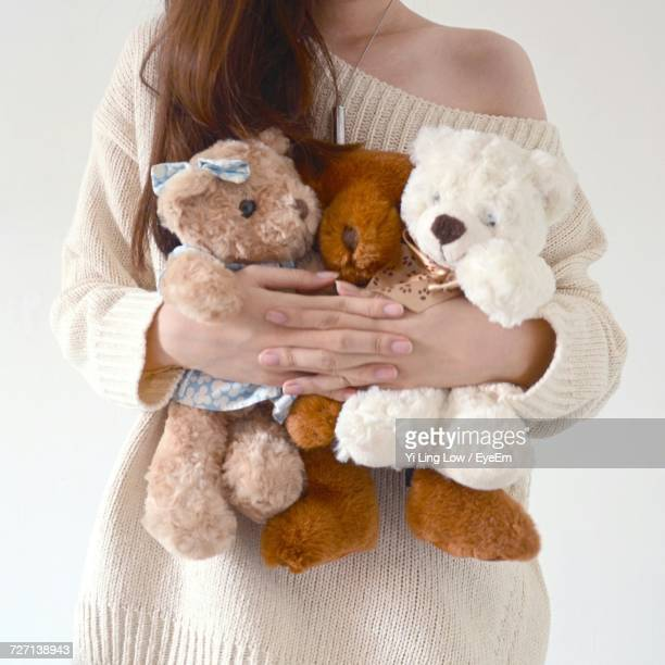 Cropped Image Of Woman Holding Stuffed Toys Against White Background