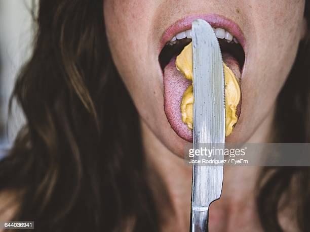 Cropped Image Of Woman Licking Peanut Butter