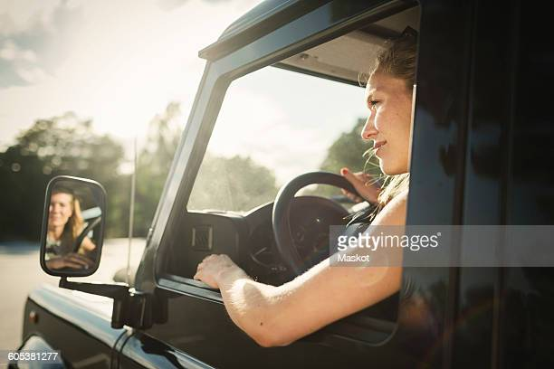 Cropped image of woman looking away while driving car