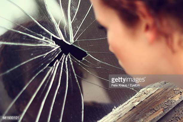 Cropped Image Of Woman Looking Through Broken Glass Window