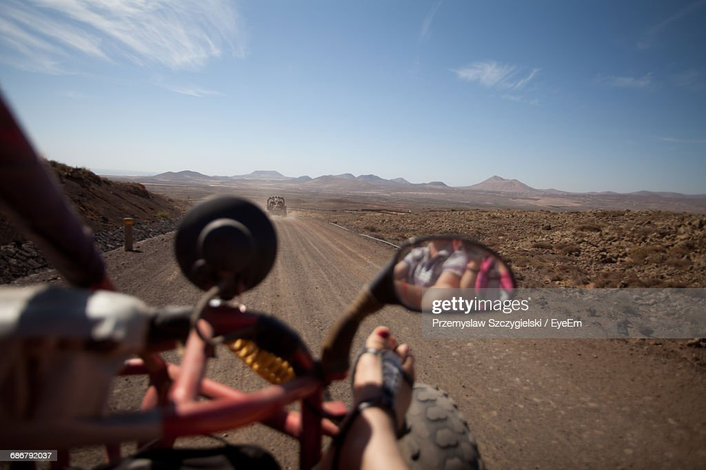 Cropped Image Of Woman On Beach Buggy Against Sky : Stock Photo