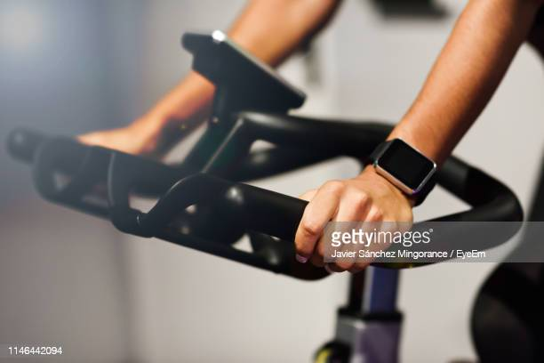 cropped image of woman on exercise bike in gym - peloton stock pictures, royalty-free photos & images