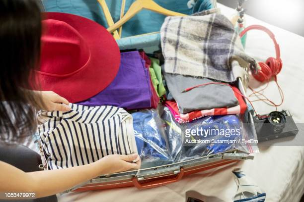 cropped image of woman packing suitcase at home - luggage stock photos and pictures