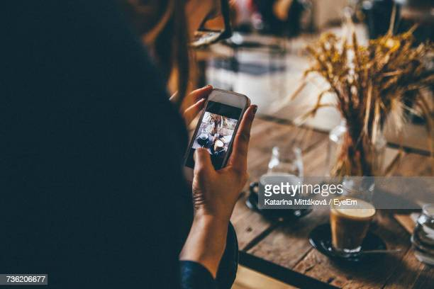 Cropped Image Of Woman Photographing Coffee Through Smart Phone At Table
