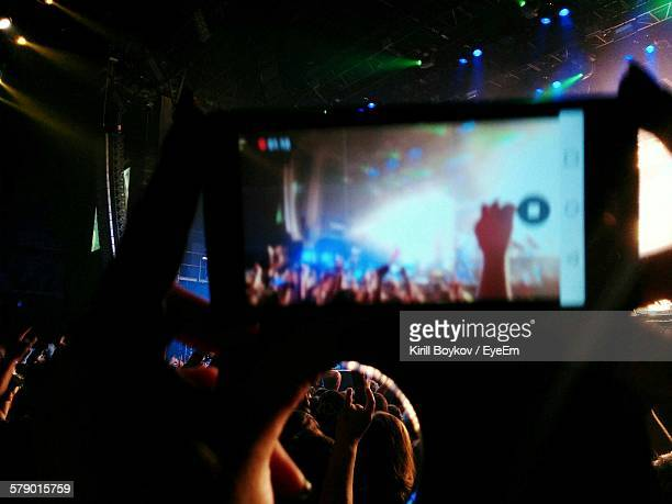 Cropped Image Of Woman Photographing Music Concert Through Smart Phone At Night