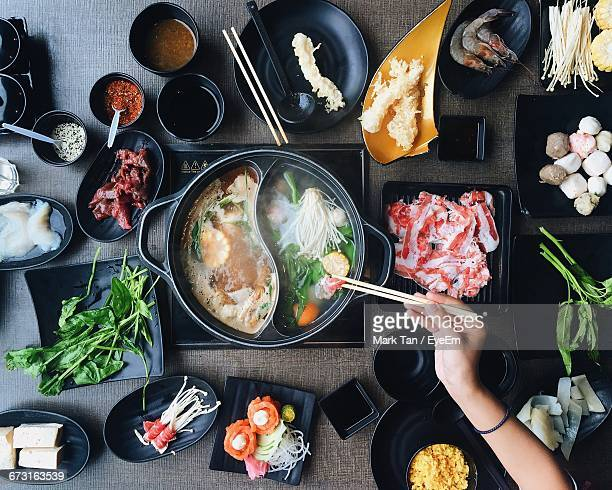 Cropped Image Of Woman Picking Food From Hot Pot On Table