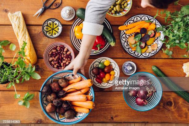 cropped image of woman picking up vegetables at wooden table - vegetarian food stock pictures, royalty-free photos & images