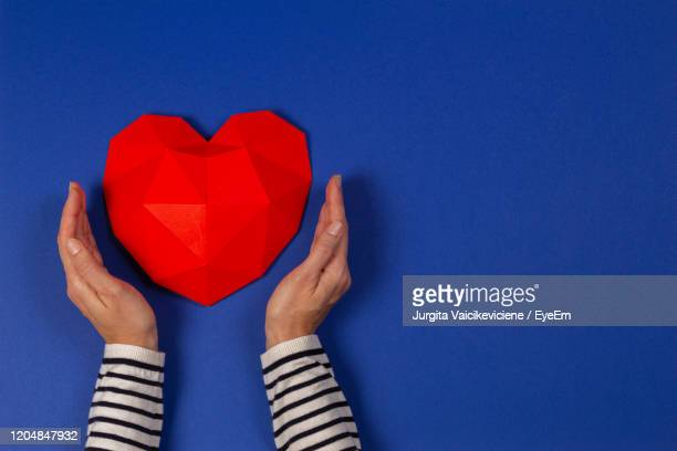 cropped image of woman placing hand near heart shape paper against blue background - sleeve stock pictures, royalty-free photos & images