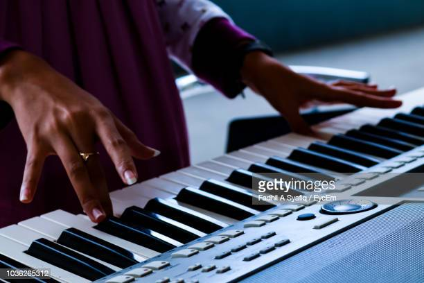 cropped image of woman playing piano - keyboard player stock photos and pictures