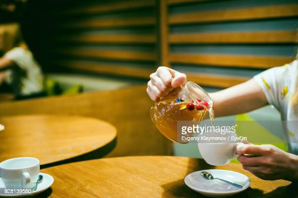 cropped image of woman pouring drink in coffee cup at restaurant - coffee drink stock pictures, royalty-free photos & images