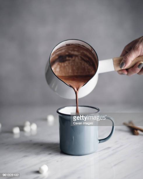 cropped image of woman pouring hot chocolate in mug on table - hot chocolate stock pictures, royalty-free photos & images