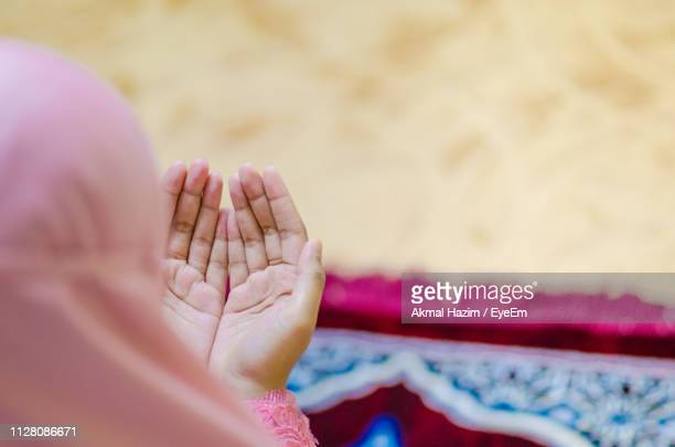 cropped image of woman praying with hands cupped - muslim praying stock pictures, royalty-free photos & images