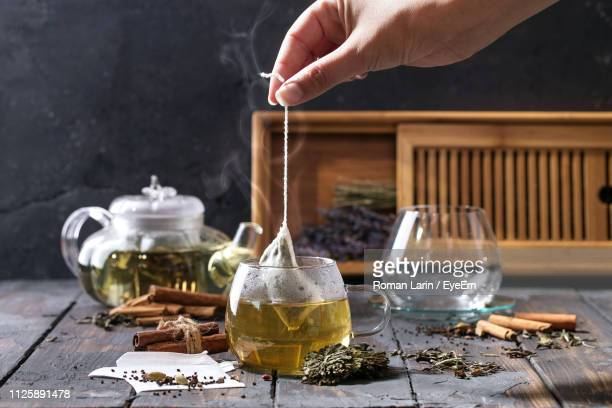cropped image of woman preparing herbal tea on table - tea leaves stock photos and pictures