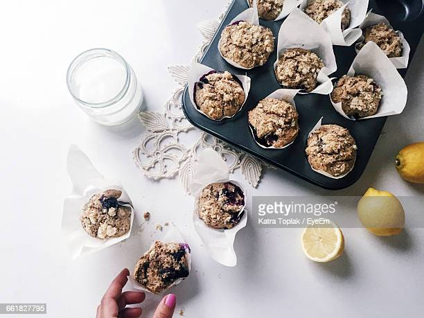 Cropped Image Of Woman Preparing Muffins At Table