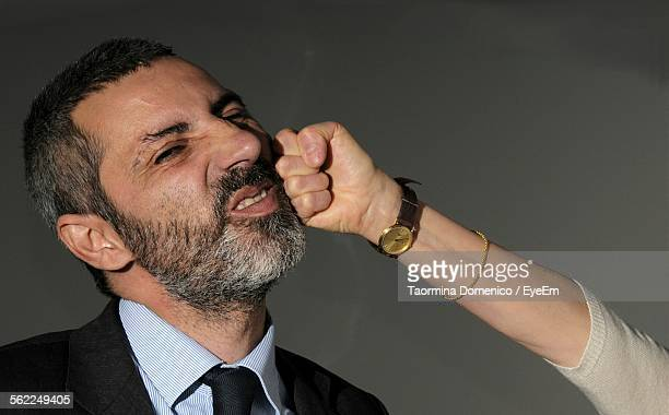 Cropped Image Of Woman Punching Businessman At Home