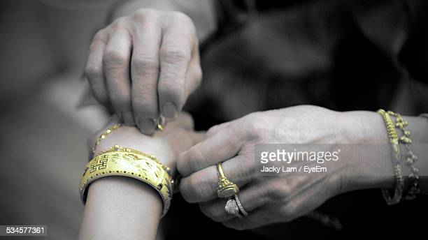 cropped image of woman putting bracelet around brides hand - バングル ストックフォトと画像