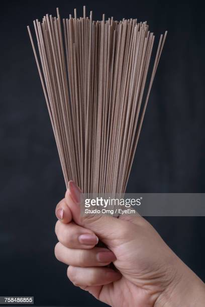 Cropped Image Of Woman Raw Soba Noodles Against Black Background