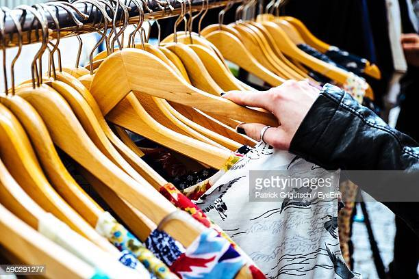 Cropped Image Of Woman Selecting Dress In Store