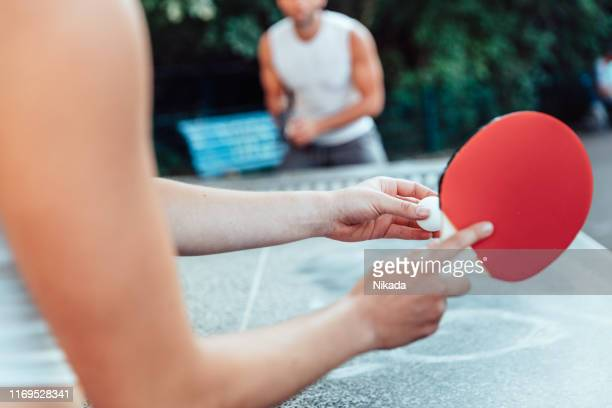 cropped image of woman serving ball on table tennis while playing with man - table tennis stock pictures, royalty-free photos & images