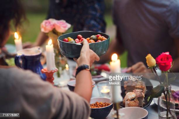 Cropped image of woman serving food to friends at garden party