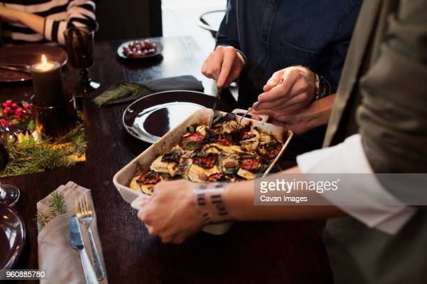 Cropped image of woman serving food to friends at table during Christmas