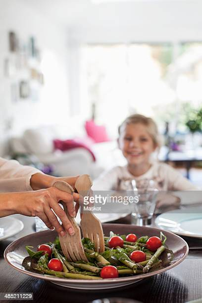 cropped image of woman serving salad at dining table - onscherpe achtergrond stockfoto's en -beelden