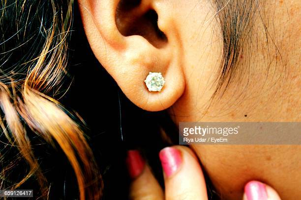 cropped image of woman showing diamond earring - skin diamond stock pictures, royalty-free photos & images