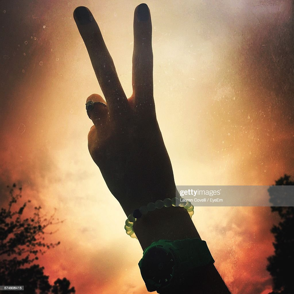 Cropped Image Of Woman Showing Peace Sign Against Sky During Sunset : Stock Photo