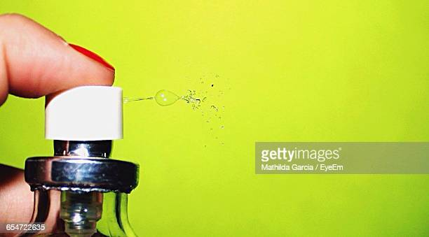 Cropped Image Of Woman Spraying Perfume Against Wall