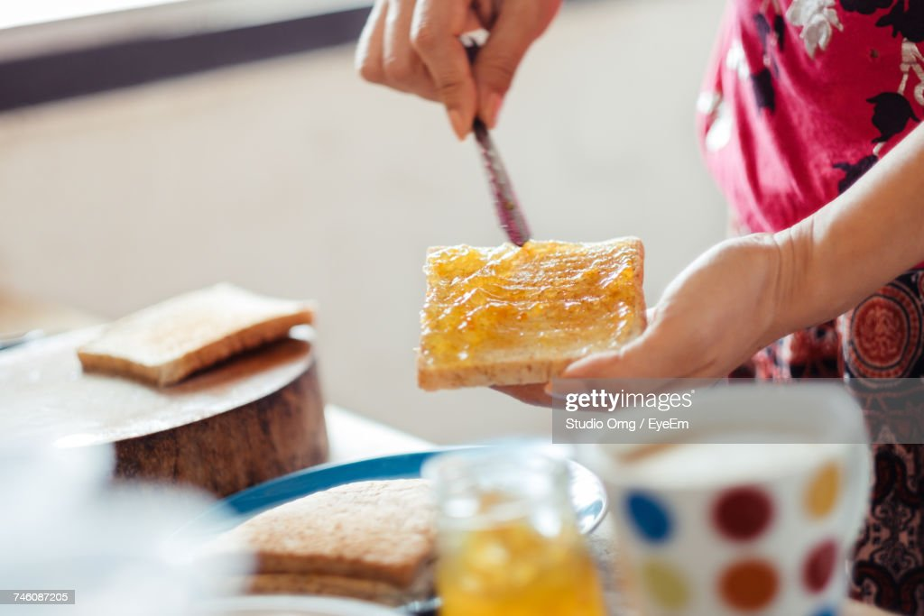 Cropped Image Of Woman Spreading Orange Jam On Bread At Home : Stock Photo