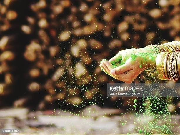 Cropped Image Of Woman Throwing Green Powder
