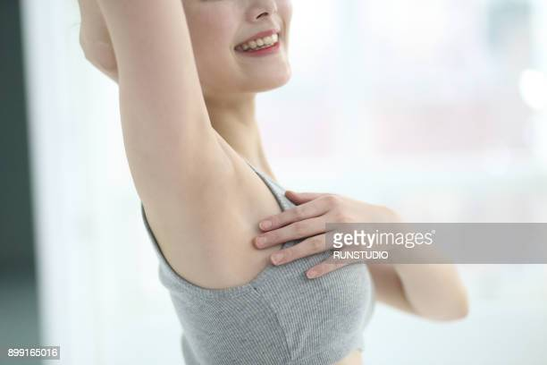 cropped image of woman touching armpit - busen nahaufnahme stock-fotos und bilder