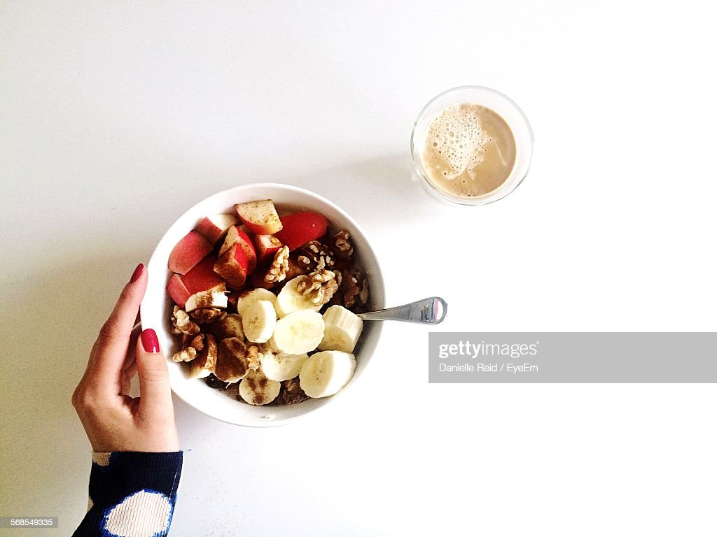 Cropped Image Of Woman Touching Bowl Of Breakfast On Table : Stock Photo