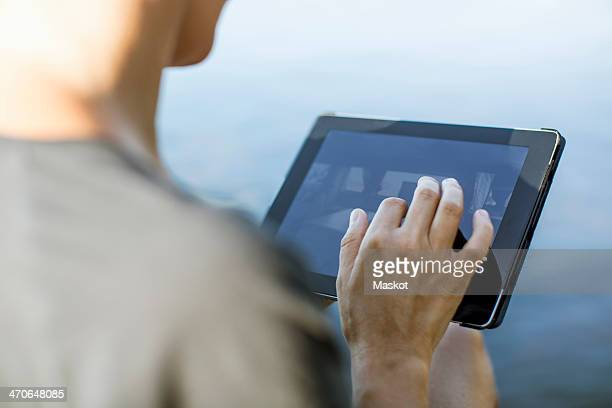 Cropped image of woman touching digital tablet outdoors