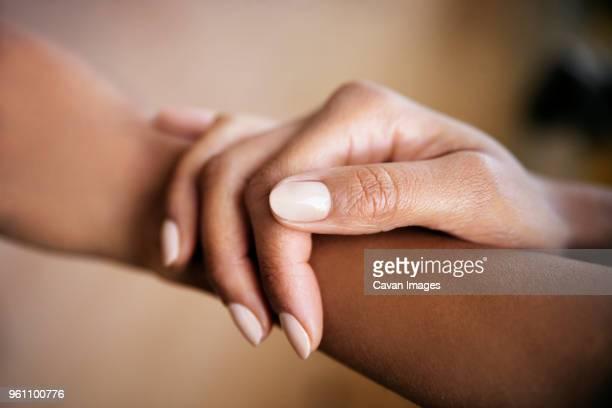 cropped image of woman touching hand - fingernail stock pictures, royalty-free photos & images