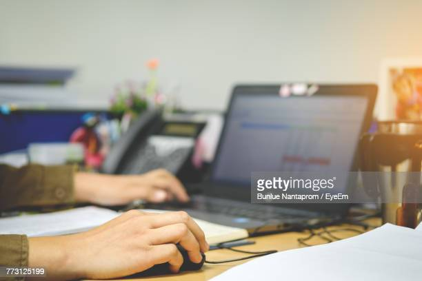 Cropped Image Of Woman Using Laptop In Office