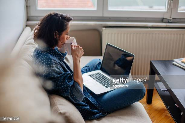 cropped image of woman using laptop with blank screen - sofa stock pictures, royalty-free photos & images