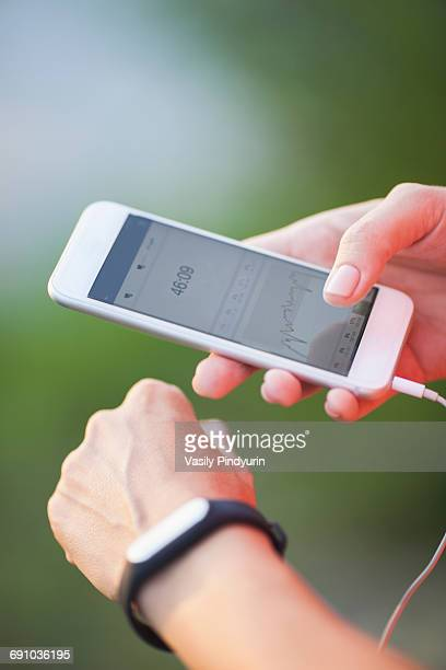 cropped image of woman using pedometer and mobile phone - muñequera fotografías e imágenes de stock
