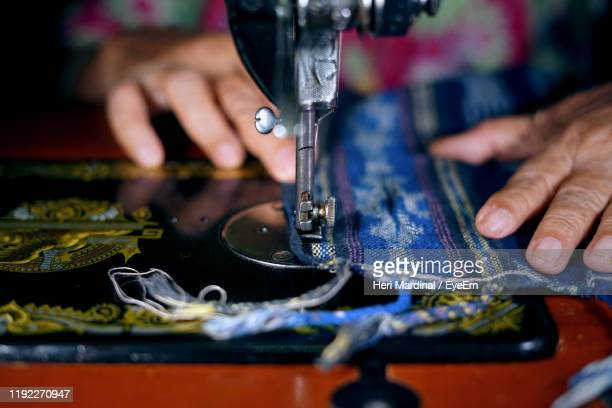 cropped image of woman using sewing machine - heri mardinal stock pictures, royalty-free photos & images