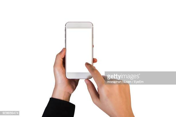 Cropped Image Of Woman Using Smart Phone Against White Background
