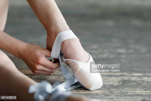 Cropped Image Of Woman Wearing Ballet Shoe On Floor