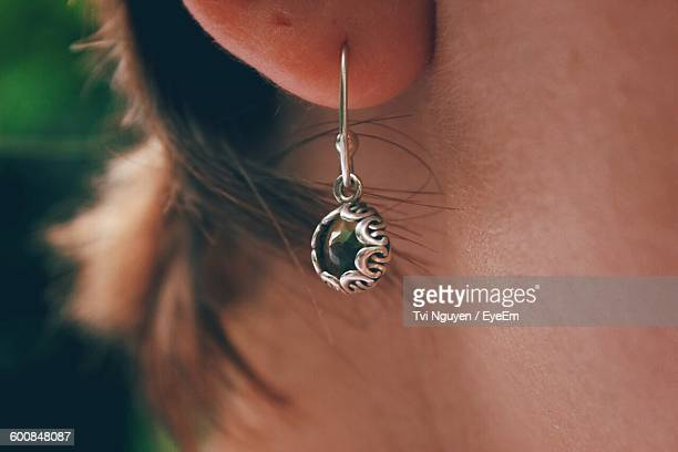 cropped image of woman wearing earring - ohrring stock-fotos und bilder