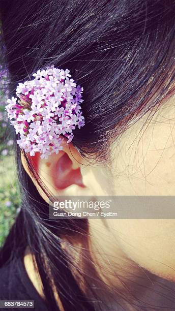 Cropped Image Of Woman Wearing Flowers On Ear
