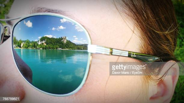 Cropped Image Of Woman Wearing Sunglasses With Reflection Of Lake